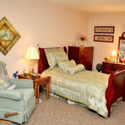 Bedroom with small bed, reclining chair and dresser
