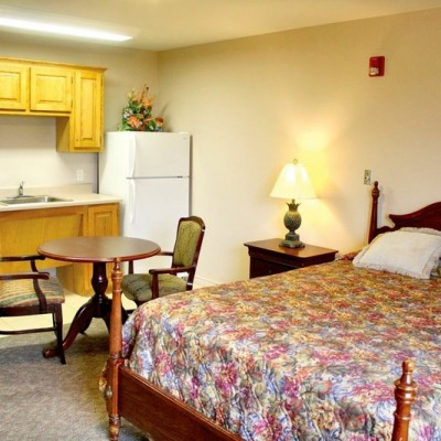 Efficiency room with bed, sink and refrigerator