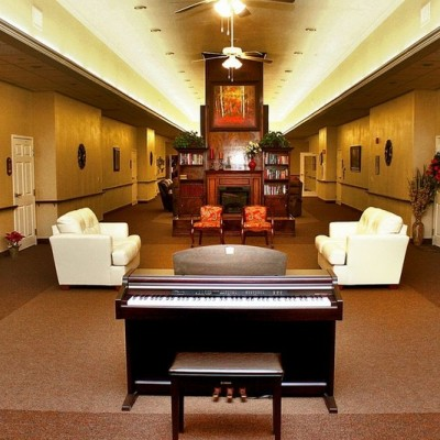 Long common area with black piano and two white couches
